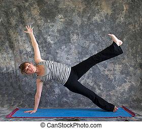 Young woman on yoga mat doing Yoga posture Vasisthasana or...