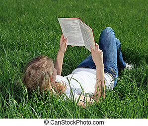 Reading a book - Attractive young woman resting outside on...