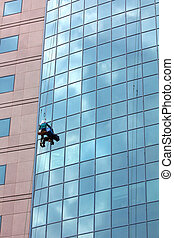 window cleaner at work - window cleaner hanging on rope at...