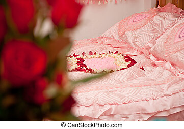 bed of love - pink wedding bed with roses on the bed