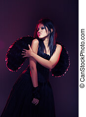 Dark angel - Brunette lady with black wings on a dark...