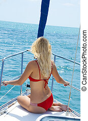 Attractive sexual woman sitting on the front of large and luxurious sailboat sailing through the tropics