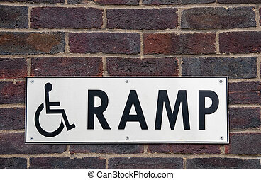 Wheelchair ramp sign on a brick wall