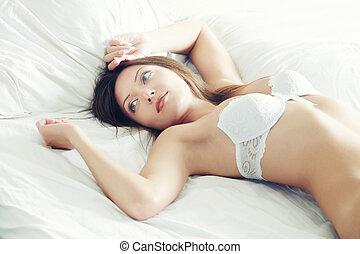 Morning - Pretty lady with white camisole laying on the bed...