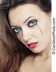 Bizarre beauty - Sad woman with odd makeup. Close-up...