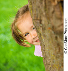 Little girl is playing hide and seek outdoors - Cute little...