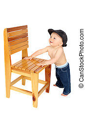 Standing baby - Cute baby boy standing up against a wooden...