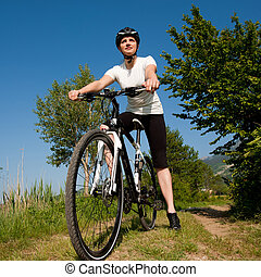Young girl riding a bike on a field path - offroad