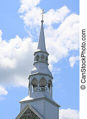 Church steeple against blue sky and white clouds