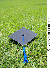 graduation gown hat on campus grass
