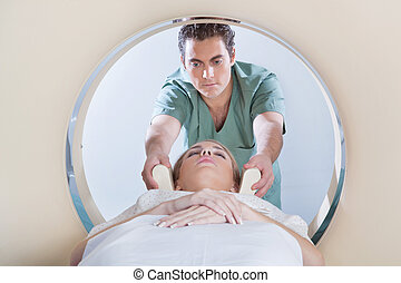 Young woman going through CT test - Nurse preparing young...