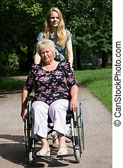 Senior woman in a wheelchair and her granddaughter