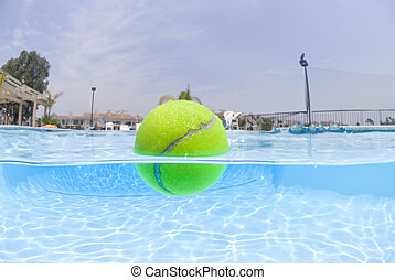 Tennis ball floating in pool - A tennis ball floats on the...