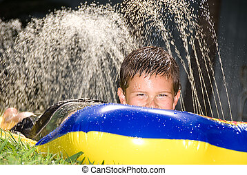 Kid on water slide - A kid slides down a slippery water...