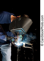 Welder and sparks - A welder fabricates a tool by attaching...