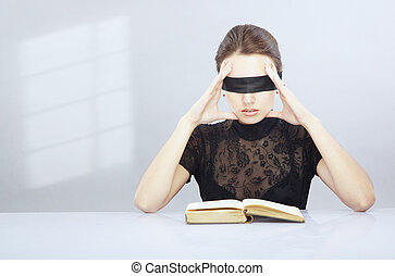 Misunderstanding - Woman with blindfold trying to read and...