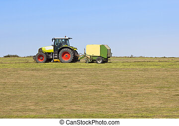haymaking time - tractor and baler working on a hilltop...