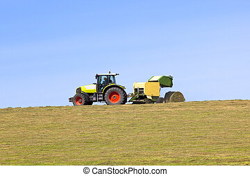 hay baling - a tractor and baler on a hillside pasture under...