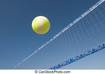 Volleyball over net - A volleyball player lobs a ball during...