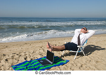 Businessman on beach with laptop - A businessman takes his...