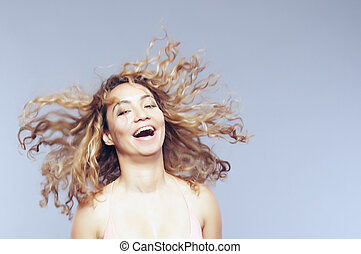 Joy - Laughing lady with curly hairstyle. Headshot in the...