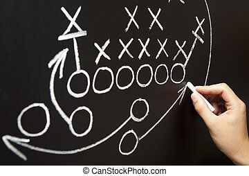 Hand drawing a game strategy with white chalk on a...