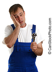 Craftsmen in blue overalls holding a box spanner