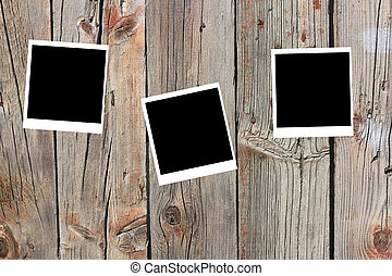 set of three old blank polaroids frames lying on a wood surface