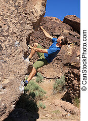 bouldering man - a man in a blue shirt bouldering on...