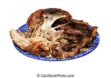 half eaten turkey carcass on a blue platter isolated on...