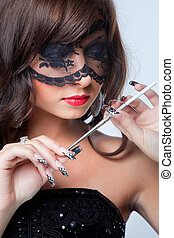 Closeup portrait of attractive young brunette girl with long dark ringlets and fine art manicure wearing lacy mask on her eyes holding graceful silver mouthpiec
