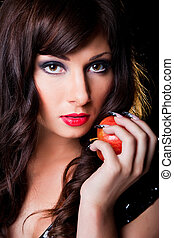 portrait of beautiful young brunette girl with long dark ringlets and fine art lacy manicure holding red apple in her hand on black background