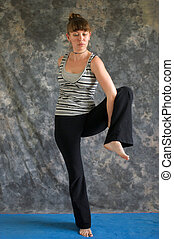 Young woman on yoga mat entering Yoga posture Bird of Paradise Pose or Tittibhasana against a grey background , facing front lit by diffused sunlight.