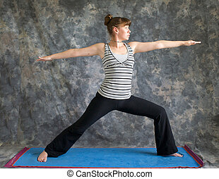 Young woman on yoga mat doing Yoga posture Virabhadrasana II or warrior 2 pose against a grey background in profile, facing right lit by diffused sunlight.