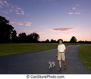 Senior man walking dog at sunset
