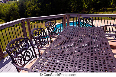 Seat and chairs on deck by swimming pool