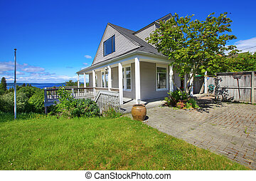 Grey house with white trim and water view.