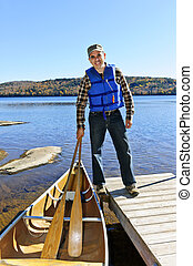 Man with canoe - Man standing on dock with canoe on Lake of...