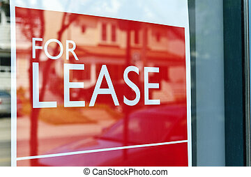 For lease sign - For Lease sign on red in window reflecting...