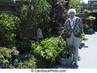 grandma in the garden - granma shwoing her garden with...