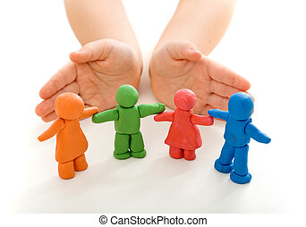 Child hands protecting clay people on white table -...
