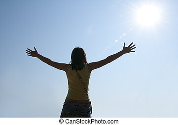 Woman with outstretched arms to the sun