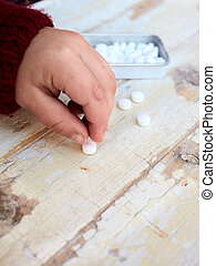 child and drugs - child picking tablet from rustic tablet -...