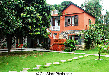 Red house with green meadows - Landscape of red guest house...
