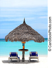 Thatched hut on a stretch of beach in Aruba overlooking the...