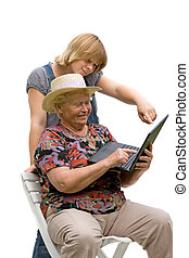 Senior woman and her granddaughter with a computer on white background