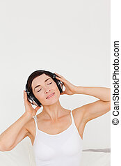 Charming woman listening to music in her bedroom
