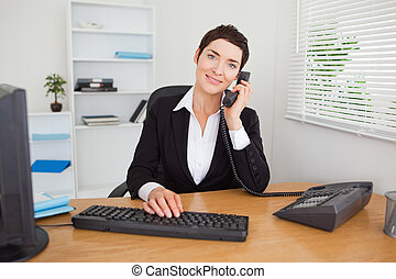 Young secretary answering the phone in her office