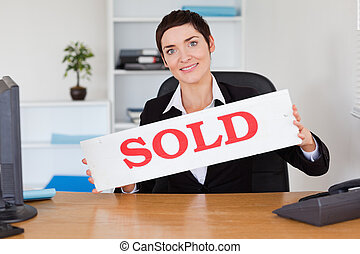 Happy real estate agent with a sold panel