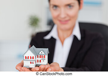 Businesswoman holding a miniature house